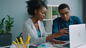 videoblocks-two-african-american-business-people-working-together-at-the-office-afro-american-businessman-and-businesswoman-talking-using-laptop-computer-checking-financial-charts-team-work_r-fv5mr